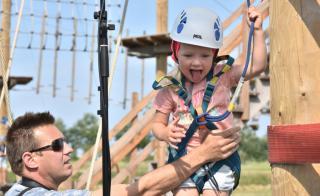 Man helpt kind bij het Klimpark