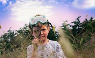 Jongetje met duikbril op dat door een vergrootglas kijkt